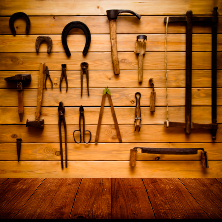 gangway: Light wooden wall with different vintage carpentry tools. Background. View from dark wooden gangway, table or bridge. Collage. Toned. Stock Photo