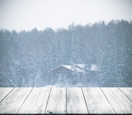 gangway: View on house in snowy winter forest from dark wooden gangway, table or bridge. Background. Toned.