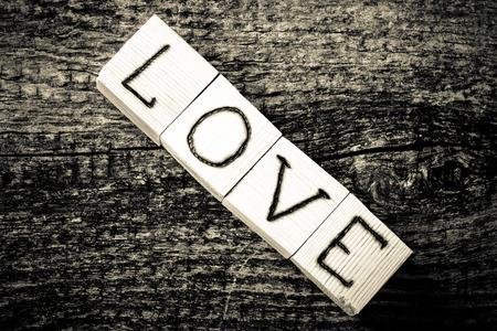 Romantische inscriptie van letters op lichte houten kubussen op een oude grijze houten achtergrond. Afgezwakt.