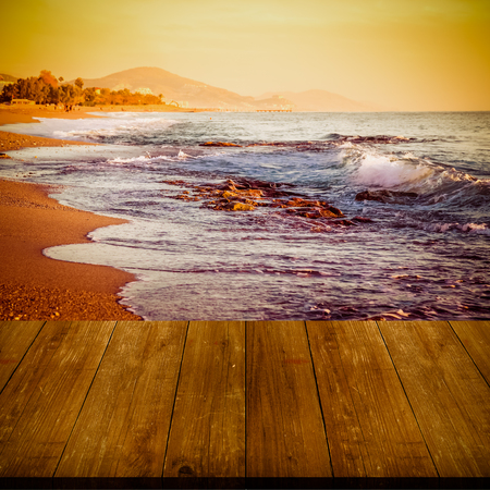 waves  pebble: View on waves on pebble beach of Mediterranean sea from dark wooden gangway, table or bridge. Turkey in autumn. Alanya. Natural background. Toned. Stock Photo