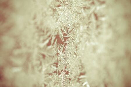 wintery snowy: Frozen patterns on a window. Winter nature background. Selective focus. Toned.
