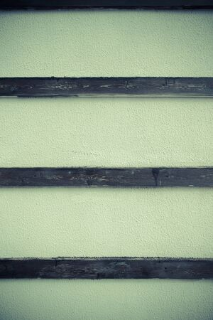 parget: Light plastered wall with wooden stripes for background. Close up detale. Toned. Stock Photo
