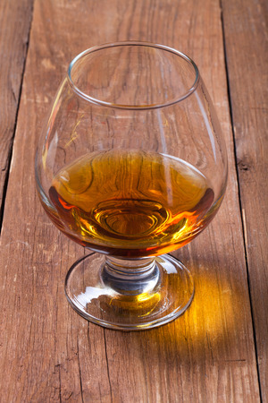 drunks: Cognac in a glass goblet on the old wooden table. Stock Photo