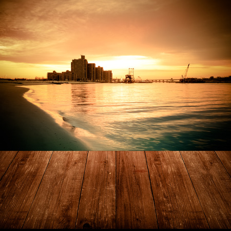 View on warm sunrise on the coast from dark wooden gangway or bridge. Collage. Overlooking the Atlantic Beach Bridge. East rockaway Intel. New-York. US East Coast. Toned. Stock Photo