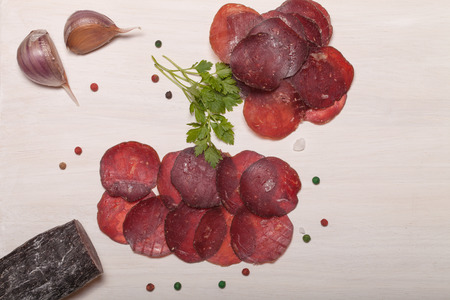 cutting horse: Sliced horse sausage, herbs and spices on cutting board.