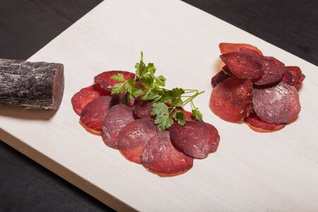 cutting horse: Sliced horse sausage, herbs and spices on cutting board. Toned.