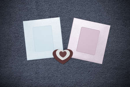 Two photoframes and space for text. Romantic love theme on jeans background. Toned.