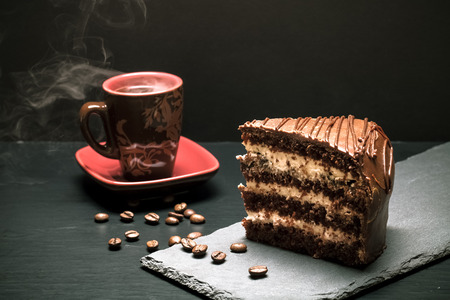 coffee and cake: A piece of chocolate cake and cup of coffee on slate plate on black background. Selective focus. Toned. Stock Photo