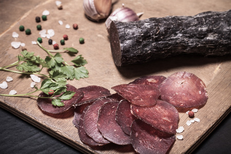 cutting horse: Sliced horse sausage, herbs and spices on cutting board. Selective focus. Toned. Stock Photo