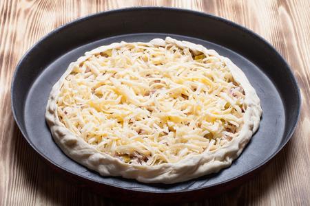 unprepared: Unprepared pizza with grated cheese.