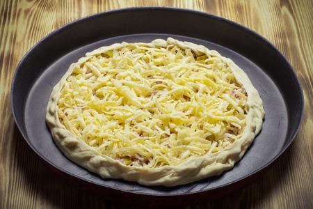 unprepared: Unprepared pizza with grated cheese. Toned.