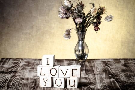 i love: Wooden cubes with inscription I LOVE YOU and bouquet of dry flowers on new wooden board and burlap background. Selective focus. Toned. Stock Photo