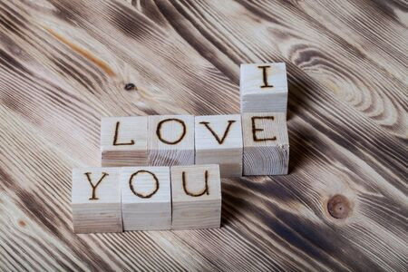 i love: Wooden cubes with inscription I LOVE YOU on new wooden background. Selective focus.