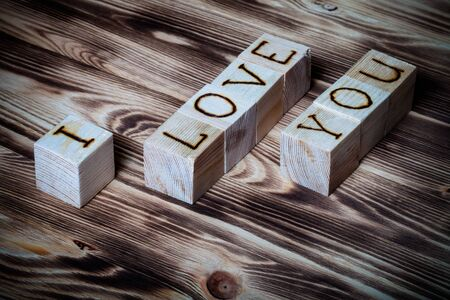 i love: Wooden cubes with inscription I LOVE YOU on new wooden background. Toned. Stock Photo
