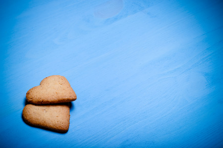 Two heart-shaped cookie on a blue wooden table. Toned.