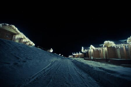 Wooden houses with garlands along the road winter night. Toned.