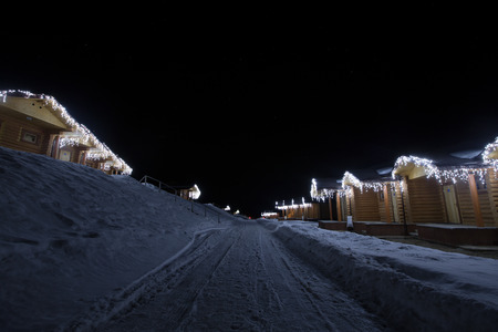 wooden houses: Wooden houses with garlands along the road winter night.
