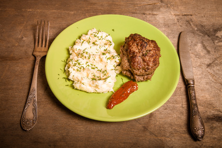 dryed: Homemade cutlet with mashed potatoes on a plate on old wooden table. Toned.
