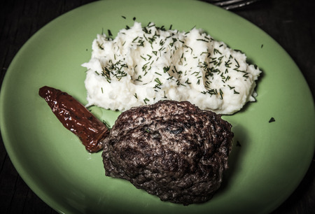 dryed: Homemade cutlet with mashed potatoes on a plate on old wooden table. Selective focus. Toned. Stock Photo