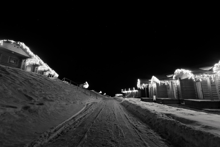 wooden houses: Wooden houses with garlands along the road winter night. Toned.