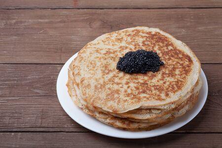 blini: Black caviar on Russian pancakes - blini. Stock Photo