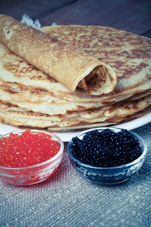blini: Russian pancakes - blini with red and black caviar. Selective focus. Toned.