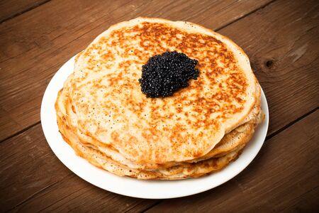 blini: Black caviar on Russian pancakes - blini. Toned. Stock Photo