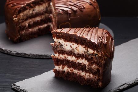 Chocolate cake on slate plate on black background. Selective focus. Stock Photo