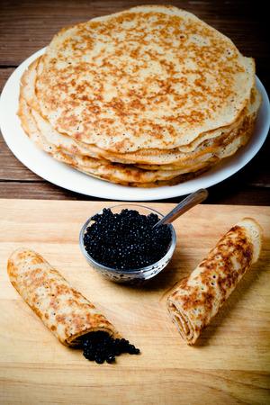 blini: Russian pancakes - blini with black caviar. Selective focus. Toned.