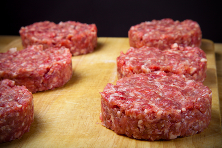 beefburger: Raw cutlet of minced meat on a wooden cutting board. Shallow depth of field. Toned.