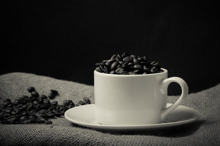 cup and saucer: Cup, saucer and coffee beans on a burlap background. Selective focus. Toned.