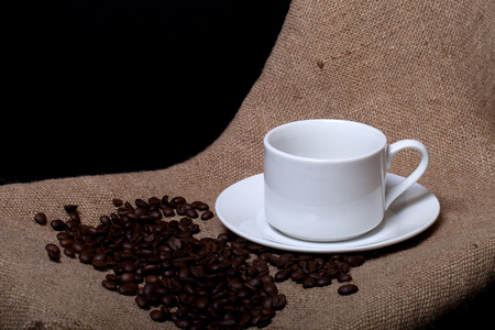 cup and saucer: Cup, saucer and coffee beans on a burlap background.