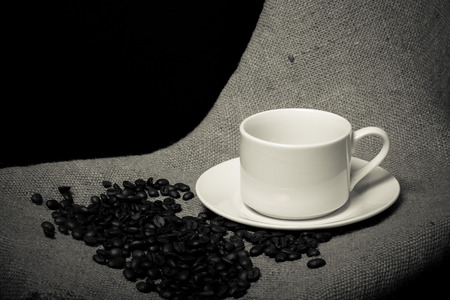 cup and saucer: Cup, saucer and coffee beans on a burlap background. Toned.