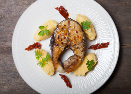 potato tuna: Fried tuna fish with mashed potato, dried tomato and parsley on light plate on old wooden table. Stock Photo
