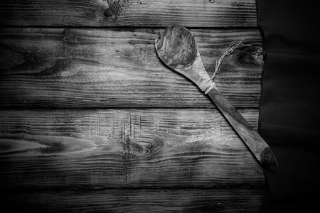 red kitchen: Red kitchen towel and wooden spoon on old wooden burned table or board for background. Toned. Stock Photo