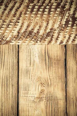 wooden surface: Knitted scarf on old wooden burned table or board for background. Toned.