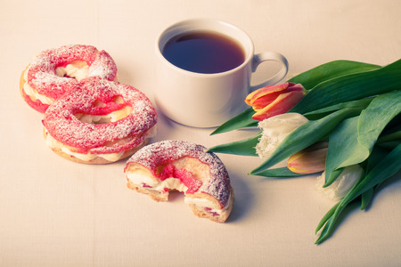 choux bun: Homemade custard cakes with cream and bunch of spring tulips on the table. Toned. Stock Photo