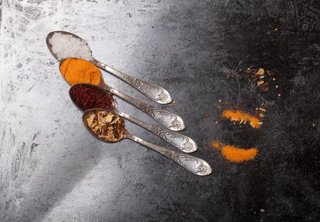 melchior: Ancient melchior spoons with spices on metal surface for background. Stock Photo