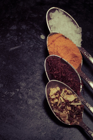 melchior: Ancient melchior spoons with spices on metal surface for background. Toned.