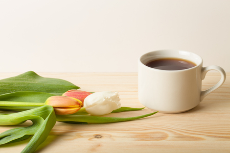 stimulated: Cup of tea and bunch of spring tulips on the table. Toned. Stock Photo
