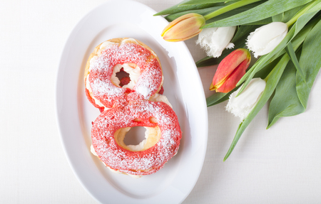 choux bun: Homemade custard cakes with cream and bunch of spring tulips on the table. Stock Photo