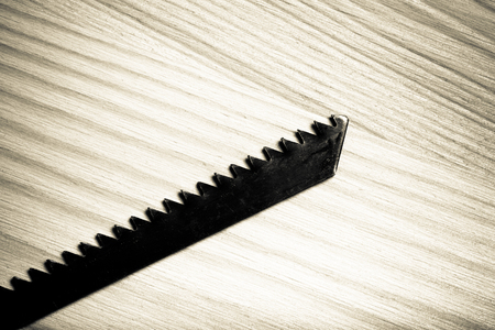woodcraft: Old saw on light wooden background. Top view. Toned.