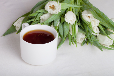 stimulated: Cup of tea and bunch of spring tulips on the table. Shallow depth of field. Selective focus.