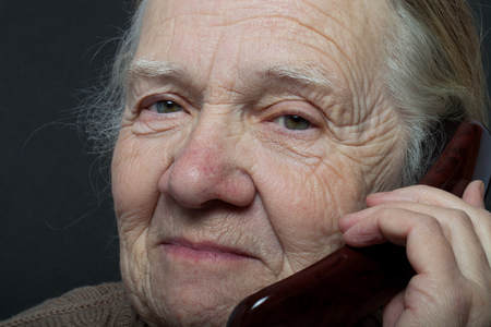 grayness: Portrait of elderly woman with telephone on dark background. Stock Photo