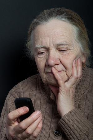 Portrait der älteren Frau mit Telefon auf dunklem Hintergrund