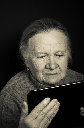 grayness: Portrait of elderly woman with tablet computer on dark background. Toned. Stock Photo
