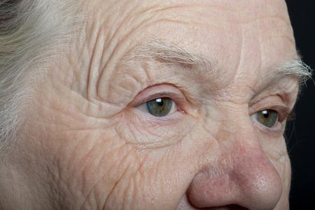 grayness: Portrait of elderly woman on dark background. Stock Photo