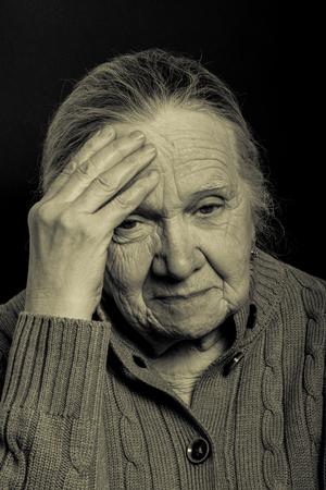 grayness: Portrait of elderly woman on dark background. Toned.