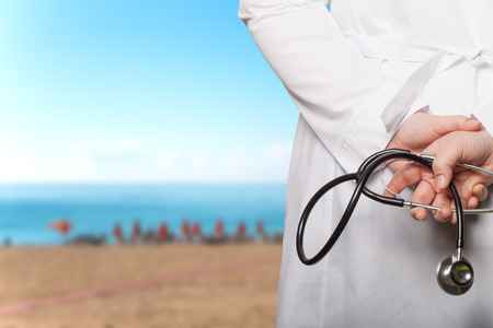 Der Arzt legte seine Hände mit Stethoskop auf dem Rücken auf einem unscharfen Hintergrund.