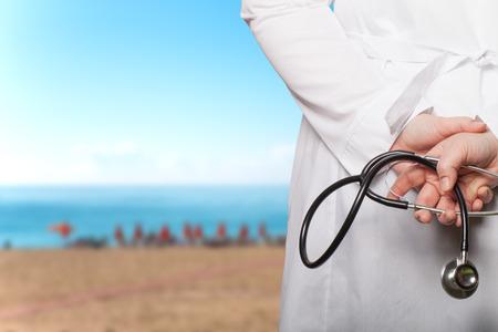 lab coat: El m�dico puso sus manos con el estetoscopio a la espalda sobre un fondo borroso. Foto de archivo